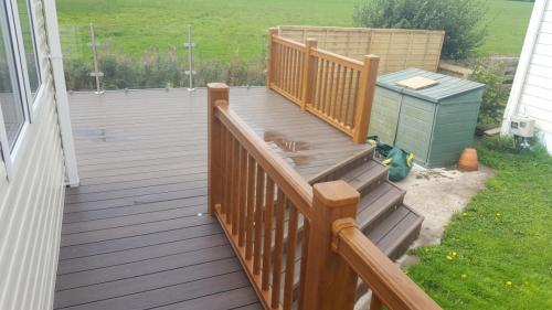 17. Walnut composite deck with golden oak plastic handrails combined with glass balustrades