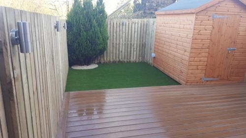 22. Teak deck with closed boards fence and artificial grass